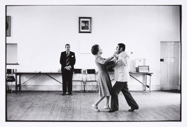 Dancing-master, Ted van Rensburg, watches two of his ballroom pupils, swinging to the music of a recording of Victor Sylvester and his Orchestra, in the hall of the Memorable Order of Tin Hats, at the old Court House (El profesor de baile, Ted van Rensbur
